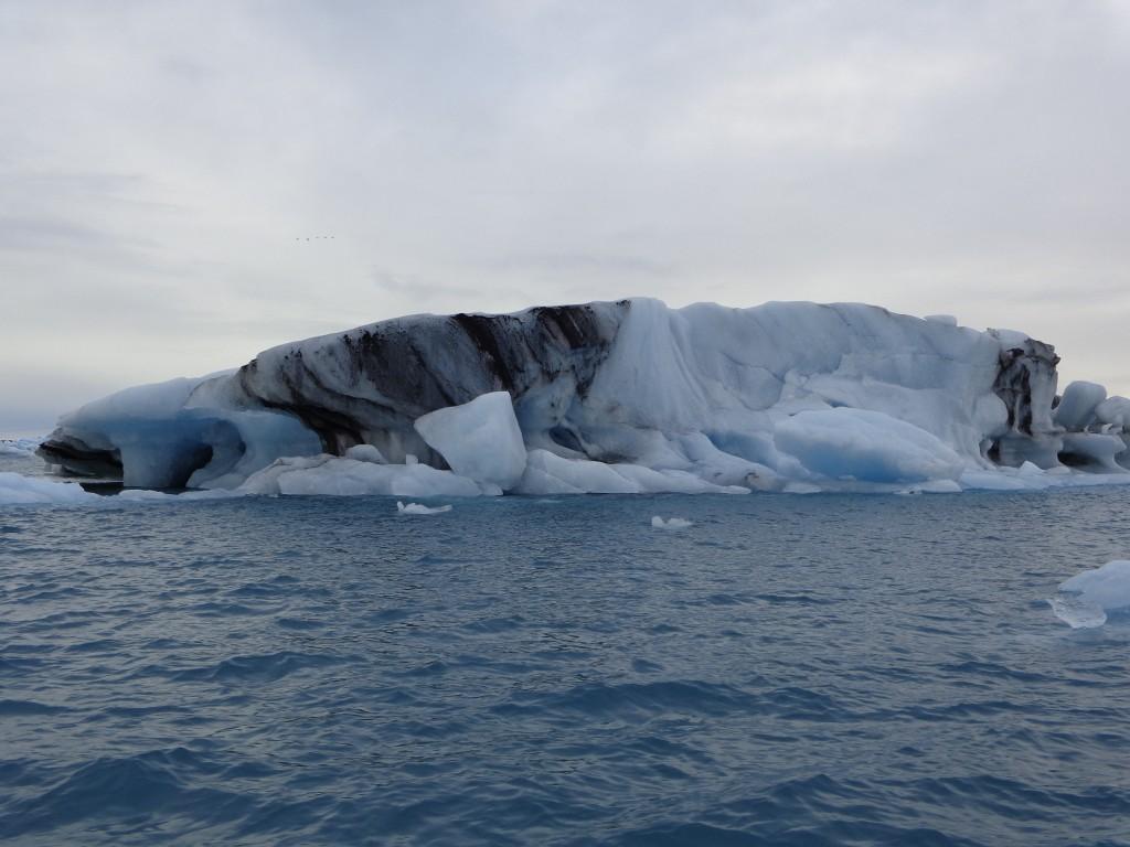 Черните следи по айсберга са от вулканична пепел
