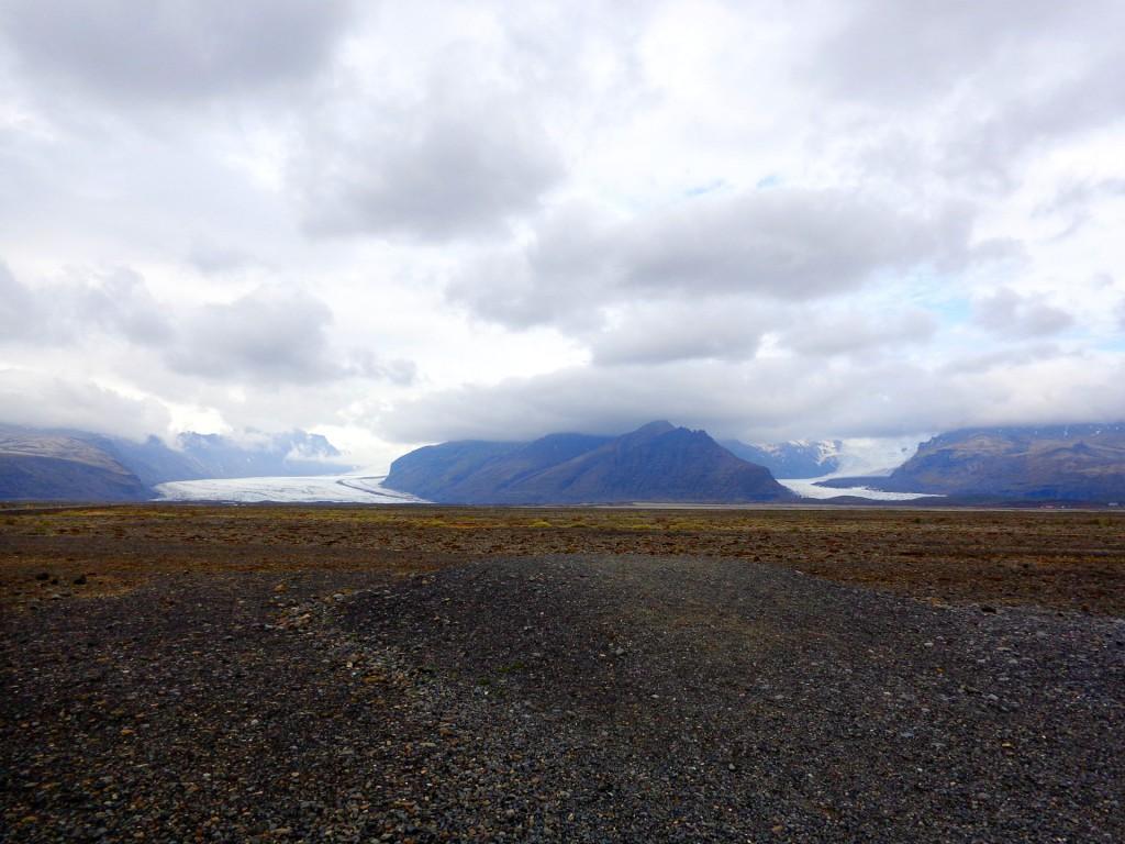 Пясъчната пустиня Скейдарарсандур с два от ледените езици на ледника Ватнайокутл. Стрит зад облаците е най-високият връх в Исландия Hvannadalshnúkur